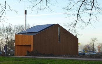 De houten warmtecentrale in de Muziekwijk heeft pv-panelen en grasdak en houtgestookte ketel